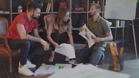 Blij startteam die de documenten van het businessplan bespreken bij vloer in bureau stock videobeelden
