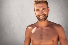 Blij topless mannetje met in kapsel en varkenshaar die het sterke lichaam builduing stellen hebben tegen grijze achtergrond met g stock foto