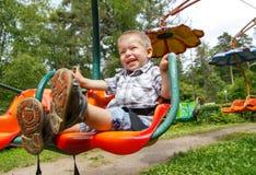 Blij weinig jongen die pret op carrousel in het park hebben Royalty-vrije Stock Foto's