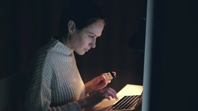 Blij wijfje die online het winkelen kopen door creditcard die notitieboekje gebruiken bij nacht stock videobeelden