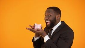 Blij zwart mannetje in het formalwear schudden piggybank, besparend geld in vertrouwende bank stock footage