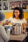 Blije aardige jonge vrouw die de soep geven royalty-vrije stock foto