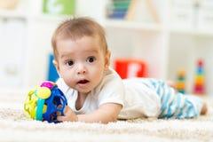 Blije baby die op het tapijt in kinderdagverblijfruimte liggen royalty-vrije stock foto's