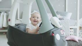 Blije baby die op thuis het zitten in stuk speelgoed auto kijken stock footage