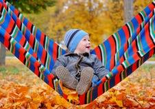 Blije babyjongen in de herfstpark op een hangmat Stock Fotografie
