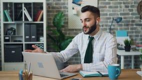 Blije beambte die videogesprek met laptop draadloze oortelefoons maken op het werk stock videobeelden
