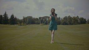 Blije blootvoetse vrouw die op groen grasgebied lopen stock video