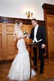 Blije bruid en bruidegom bij huwelijksregistratie Stock Foto