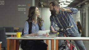 Blije collega's die in de werkplaats babbelen De succesvolle beambten delen het nieuws Gebaarde mens op een fiets en stock videobeelden