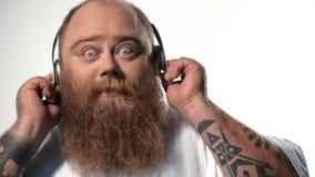 Blije dikke kerel die aan favoriet lied luisteren stock footage