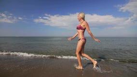Blije Europese verschijningsjongen in rode borrels die op het strand aan zijn moeder lopen die omhelst en draait stock video