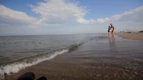 Blije Europese verschijningsjongen in rode borrels die op het strand aan zijn moeder lopen die omhelst en draait Langzame Motie stock video