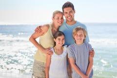 Blije familie bij het strand stock afbeeldingen