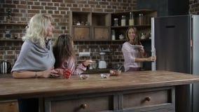 Blije familie die koekjes in keuken wachten op te proeven stock video