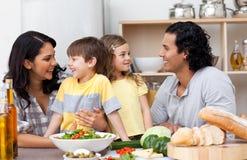 Blije familie die pret in de keuken heeft Stock Foto's