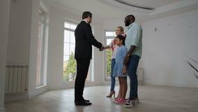 Blije familie die sleutels van makelaar het kopen huis nemen stock video