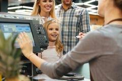 Blije familie die voor hun kruidenierswinkels betalen royalty-vrije stock afbeeldingen