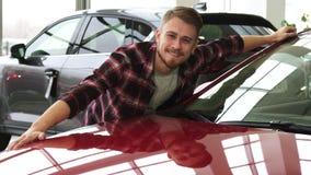 Blije gebaarde knappe mens die zijn nieuwe auto omhelzen bij de het handel drijvensalon royalty-vrije stock fotografie