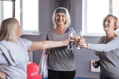 Blije gelukkige vrouwen die flessen met water houden royalty-vrije stock foto's