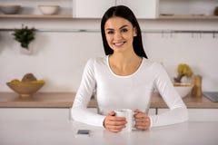 Blije het glimlachen vrouw het drinken thee in de keuken royalty-vrije stock foto's