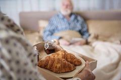 Blije hogere man en vrouw die ontbijt hebben thuis stock fotografie