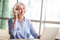 Blije hogere vrouw die op celtelefoon spreken Royalty-vrije Stock Foto