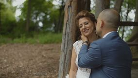 Blije huwelijksmensen die gelukkig in gazebo in het bos voelen stock footage