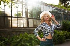 Blije jonge dame die hoed en het in uitrusting stellen dragen dichtbij Stock Fotografie