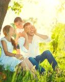Blije jonge familie die pret hebben in openlucht stock afbeelding