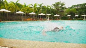 Blije jonge knappe mens die in de pool, op vakantie bij het hotel springen De reisconcept van de de zomervakantie stock video
