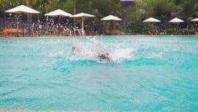 Blije jonge knappe mens die in de pool, op vakantie bij het hotel springen De reisconcept van de de zomervakantie stock videobeelden