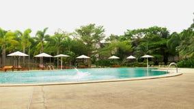Blije jonge knappe mens die in de pool, op vakantie bij het hotel springen De reisconcept van de de zomervakantie stock footage