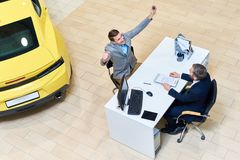 Blije Jonge Mens die Nieuwe Auto vieren stock afbeeldingen