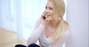 Blije jonge vrouw die op mobiel haar babbelen stock video