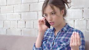 Blije jonge vrouw die op mobiele telefoon thuis spreken stock videobeelden