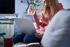 Blije jonge vrouw in roze hoodie die laptop thuis met behulp van royalty-vrije stock foto