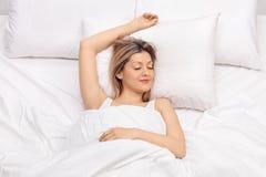Blije jonge vrouwenslaap op een bed stock afbeelding