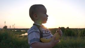 Blije jongen die met een banaan op het de zomergebied bij zonsondergang in langzame motie lopen stock footage