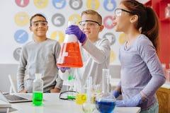 Blije jongens opheffende fles en het tonen van aan de gang zijnde reactie op klasgenoten stock foto