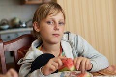 Blije jongenszitting bij een lijst en het eten van watermeloen royalty-vrije stock afbeelding
