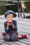 Blije jongenszitting met appel Stock Foto
