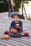 Blije jongenszitting met pompoenen en appelen Royalty-vrije Stock Foto