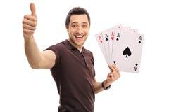 Blije kerel die een duim maken omhoog ondertekenen en vier azen houden Stock Foto