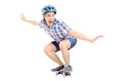 Blije kerel die een klein skateboard berijden Stock Foto's