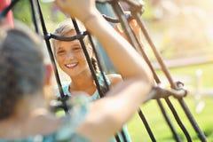 Blije kinderen die pret op speelplaats hebben Royalty-vrije Stock Afbeelding