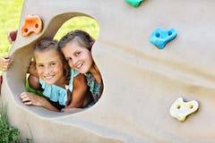 Blije kinderen die pret op speelplaats hebben Stock Fotografie