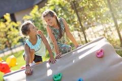 Blije kinderen die pret op speelplaats hebben Stock Foto's