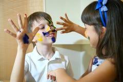 Blije kinderen met verven op hun gezichten De gezichten van kinderenverven met kleuren Royalty-vrije Stock Foto's