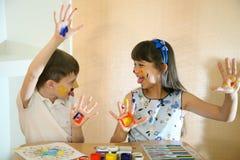Blije kinderen met verven op hun gezichten De gezichten van kinderenverven met kleuren Stock Foto