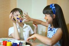 Blije kinderen met verven op hun gezichten De gezichten van kinderenverven met kleuren Royalty-vrije Stock Fotografie